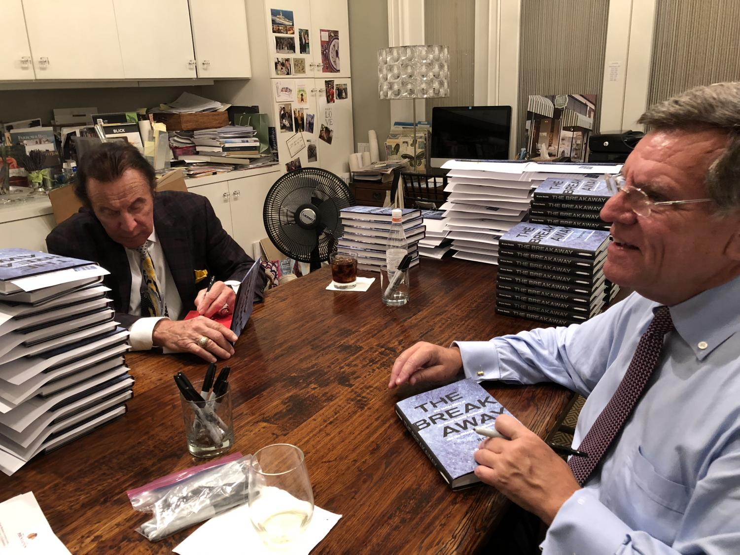 "Tony Esposito (left) and Rocky Wirtz (right) sign copies of ""The Breakaway"" at local Maze Home store"