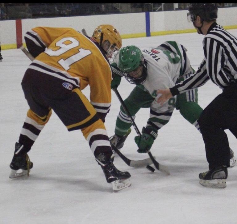 New Trier's JT Travis takes a draw against Loyola's Glynn Elliot