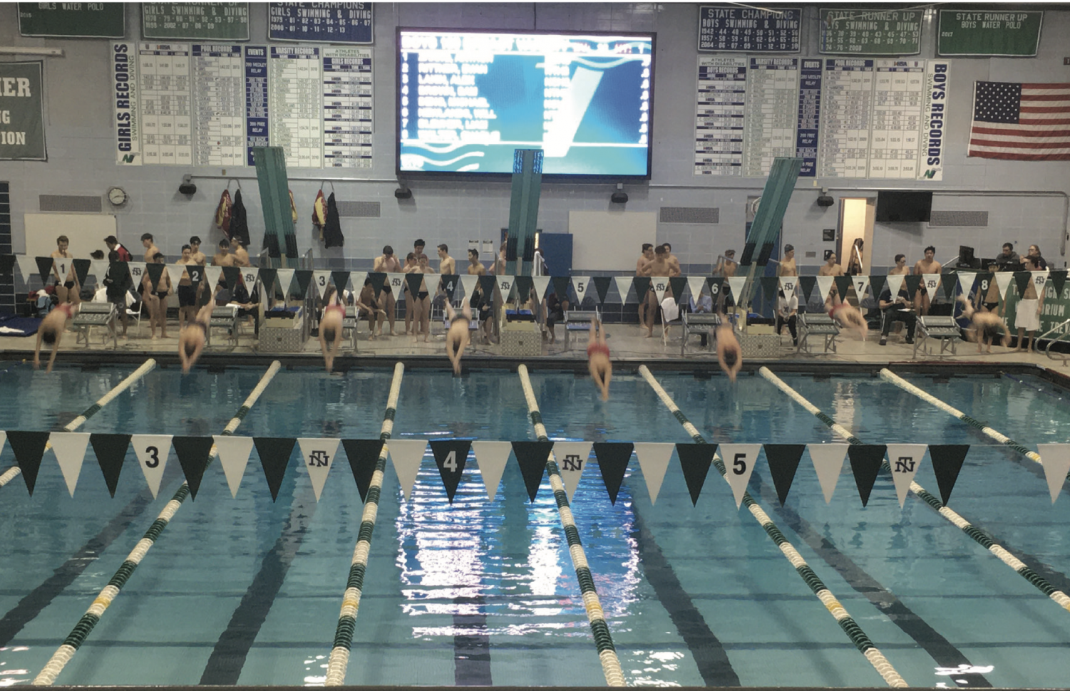 The swimmers begin the 100-yard varsity breaststroke race, which was won by sophomore Sam Brown