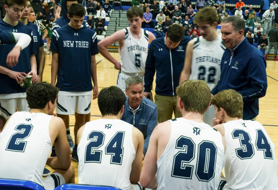 The basketball team regroups with head coach Scott Fricke at their final game against Evanston on Mar. 6