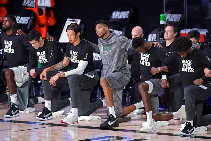 Milwaukee Bucks' Giannis Antetokounmpo kneels with teammates during the national anthem