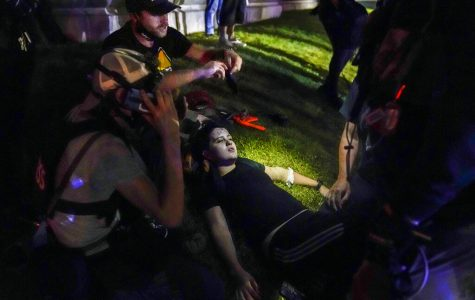 Gaige Grosskreutz, top, tends to an injured protester during clashes with police outside the Kenosha County Courthouse in Kenosha, Wis. on Aug. 25. Within minutes, Grosskreutz was shot, Prosecutors say, by 17-year-old Kyle Rittenhouse