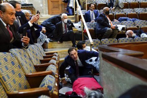 Members of Congress shelter in the House gallery as rioters try to break into the U.S. Capitol on Wednesday, Jan. 6