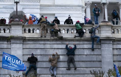 Trump supporters and right wing rioters climb the West wall of the Capitol, attempting to nullify President-elect Biden