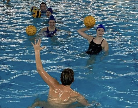 A group of socially distanced, water polo players line up to shoot against a goalie at a recent practice