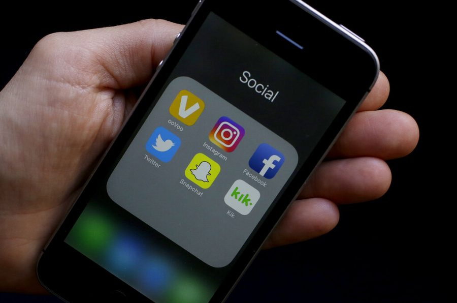 This photo shows social media app icons on a smartphone held by an Associated Press reporter