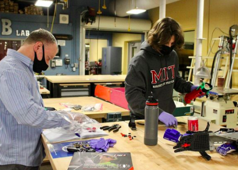 Luka Schulmeyer (right) and Chip Finck (left) build a prosthetic arm during a Robotics Club Meeting