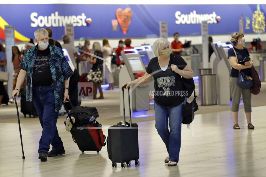 At Tampa International Airport, travelers outfitted in protective face masks make their way past the ticket counter. Many major airlines, including United and American Airlines, require masks for travel.