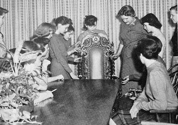 An interior design elective class meets in 1958. Seemingly all-female, the class examines furniture in the photo shown above.